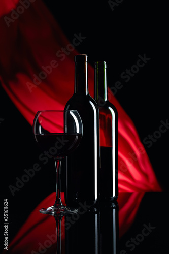 Fotografie, Obraz Wineglass and bottles of red wine on a black reflective background