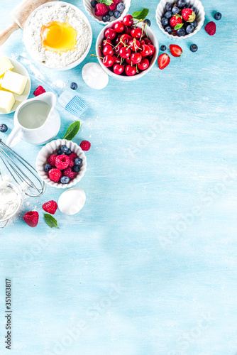 Fototapeta Berry cake baking recipe. Summer cooking baking background with assorted berries, baking ingredients, tools and utensils, light blue sun lighted wooden background flat lay top view copy space obraz
