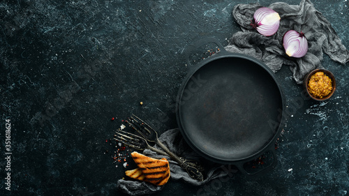 Fotografie, Obraz Black frying pan on stone background with vegetables and spices