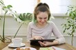 Teenager girl studying at home, student sitting at table using digital tablet