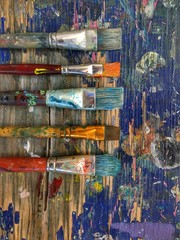 Directly Above Shot Of Messy Paintbrushes On Dirty Wooden Table