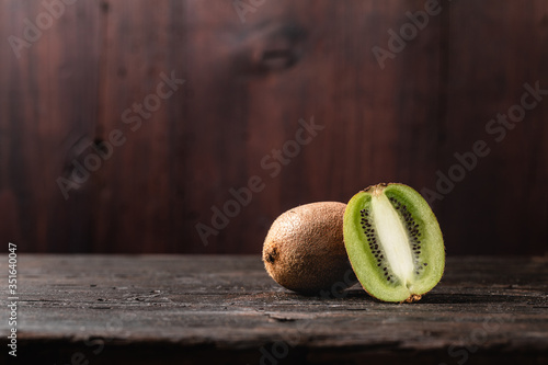 Kiwi fruits on a wooden background : A kiwi fruit and half a kiwi fruit are arranged on a rustic wooden board, natural light coming from a window to their left Fotobehang