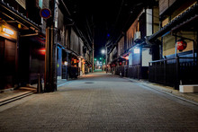 Empty Road Along Buildings At Night