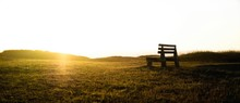 Bench On Grassy Field Against Clear Sky