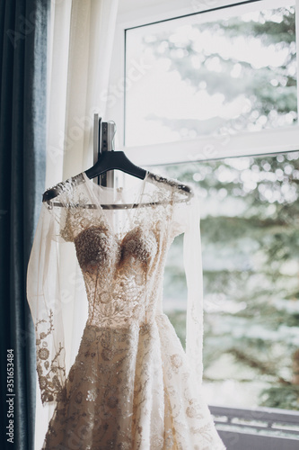 Modern wedding dress hanging at window in soft morning light. Stylish luxury beige wedding gown with lace floral pattern in light. Bridal morning preparations and boudoir