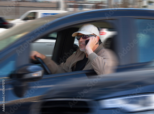 Careless male driver with sunglasses and cap using mobile phone while driving in heavy traffic Принти на полотні