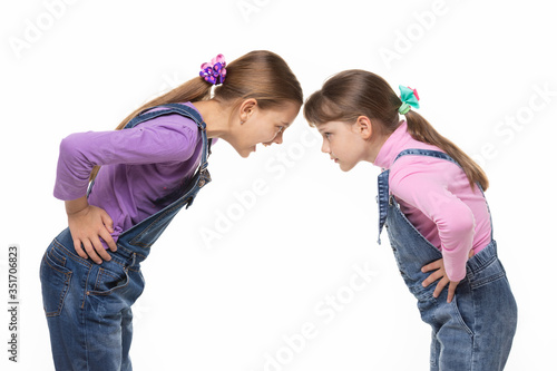 Girl yells at younger sister during altercation on white background Canvas Print