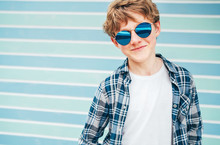 Blonde Hair 12 Year Old Caucasian Teenager Boy Fashion Portrait Dressed White T-shirt With Checkered Shirt In Blue Sunglasses With Turquoise Blue Background Wall Background. Teens Fashion Concept.