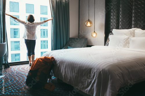 Obraz Backpacker female accomodating in 5 stars luxury hotel. She opening a whole wall window curtains to bring a day light into room. Solo traveling with backpack or home returning concept image. - fototapety do salonu