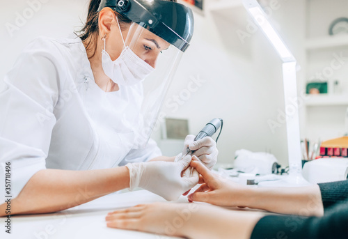 Obraz Small business existence at COVID-19 lockdown concept. Professional manicure master in Transparent Safety Face Shield using Electric Nail Polisher Tool for Glazing treatment manicure procedure. - fototapety do salonu