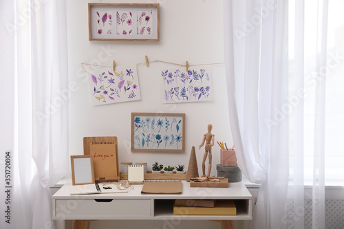 Obraz Stylish room interior with creative workplace near white wall - fototapety do salonu