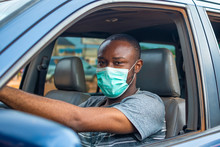 Young African Man Driving A Car Wearing A Face Mask