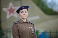 A Young Female Pilot In Uniform Of Soviet Army Pilots During The World War II. Military Shirt With Shoulder Straps Of A Major And A Beret. Against The Background Of A Military Aircraft.