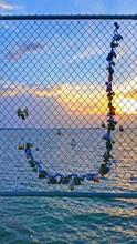 Padlocks On Chainlink Fence Against Lake Murray During Sunset