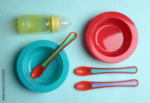 Obraz Set of colorful plastic dishware on light blue background, flat lay. Serving baby food - fototapety do salonu