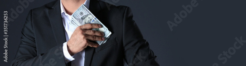 Man putting bribe into pocket on black background, closeup with space for text Canvas