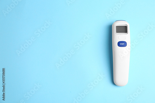 Obraz Modern non-contact infrared thermometer on light blue background, top view. Space for text - fototapety do salonu