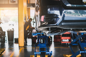 car in for service mot replacing wheel and repairment, in vehicle work shop with suspension, tools and equipment fixing broken parts, concept of repair, auto mechanic shop and car external interior