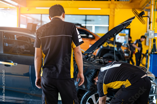 Obraz car automobile mechanic working on repairing the wheel tire of vehicle, taking car in for service workshop for male car mechanic fixing problems replacing broken parts of using tools and equipment - fototapety do salonu