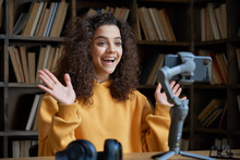 Excited Hispanic Teen Girl Social Media Channel Blogger Recording Vlog On Digital Smartphone Cam In Library. School Student Vlogger Talking Looking At Mobile Phone On Tripod Shooting Blog, Streaming.