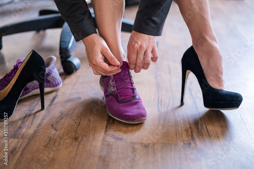 A business woman exchanges high heels for comfortable shoes in the workplace Canvas Print