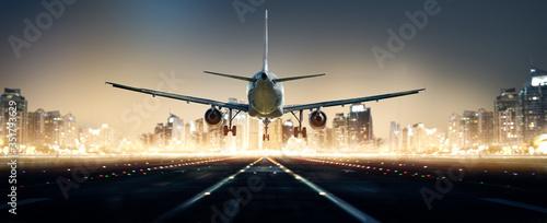 Fotografia Flugzeug landet bei Nacht in einer Großstadt