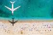 Sommer Reisekonzept mit einem Flugzeug welches über einen vollen Strand mit Menschen und türkisem Meer fliegt