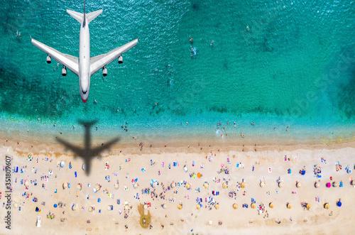 Obraz Sommer Reisekonzept mit einem Flugzeug welches über einen vollen Strand mit Menschen und türkisem Meer fliegt - fototapety do salonu