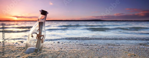 romantic sunset at the beach with bottle with a message Fototapeta