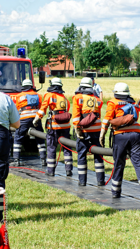 Fotografiet Firefighters Holding Pipe On Road Amidst Grass Field