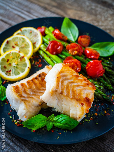 Obraz Fish dish - fried cod fillet with asparagus on wooden table  - fototapety do salonu