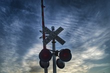 Low Angle View Of Railroad Crossing Against Sky At Dusk