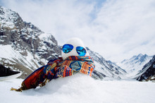 A Stylish Snowman With A Tribal Scarf And Blue Reflective Sunglasses With An Epic Blurry Mountain Background Partially Covered In Snow And A Small Lake.