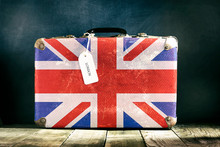 Old Suitcase With English Flag On Wooden Background.