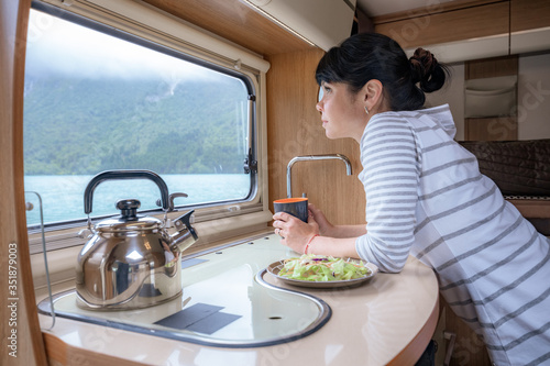 Obraz Woman in the interior of a camper RV motorhome with a cup of coffee looking at nature. - fototapety do salonu