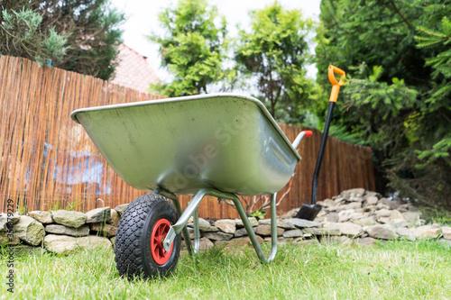 Billede på lærred Wheelbarrow On Field In Yard