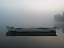 Empty Boat Moored On Calm Lake During Foggy Weather