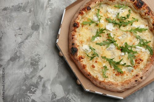 Delicious cheese pizza with arugula in takeout box on grey table, top view