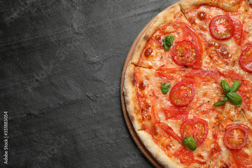 Delicious pizza Margherita on dark grey table, top view. Space for text