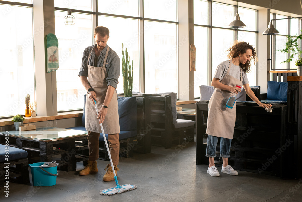 Fototapeta Two owners of restaurant or cafe washing the floor and desinfecting furniture