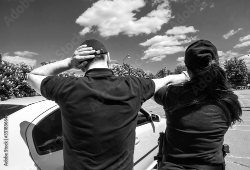 Obraz na plátně Rear View Of Policewoman Arresting Man On Street