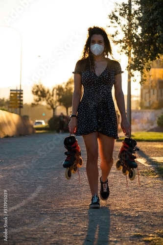 Photo Young woman adapting to the new normal walks with her skates on her hands while