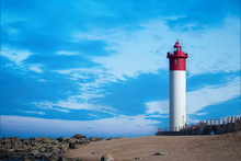 Coastal Seascape Against Famous Red And White Lighthouse And Blue Sky In The Evening, Umhlanga Near Durban, South Africa.