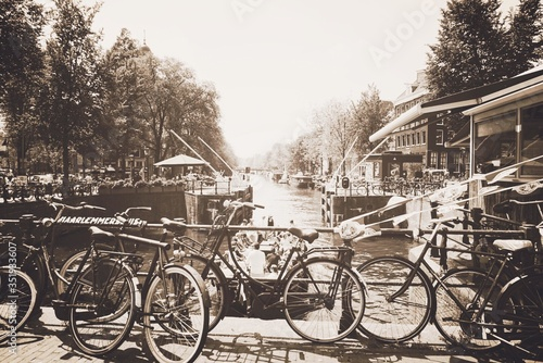 Bicycles On Boardwalk By Canal And Houses Against Clear Sky #351933607