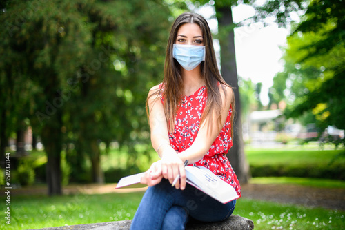Obraz Beautiful female college student reading a book on a bench in a park and wearing a mask in coronavirus times - fototapety do salonu