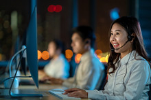 Candid Of Young Happy Asian Woman Call Centre Sitting In Office At Night Shift Overtime In Concept Telesale, Teleservice, Telemarketing, Coronavirus Information Center, Bank Or Airline Representative