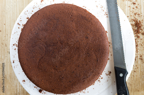 Photo Top view of baked chocolate sponge cake on white plate on the wooden background