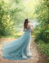 Fairy Tale Princess In Light Summer Blue, Turquoise Dress Standing In Park. Happy Woman Walks Towards Wind, Graceful Dancing Girl Goddess In Image Of Flower. Flying Long Hem Of Dress. Nymph Of Forest