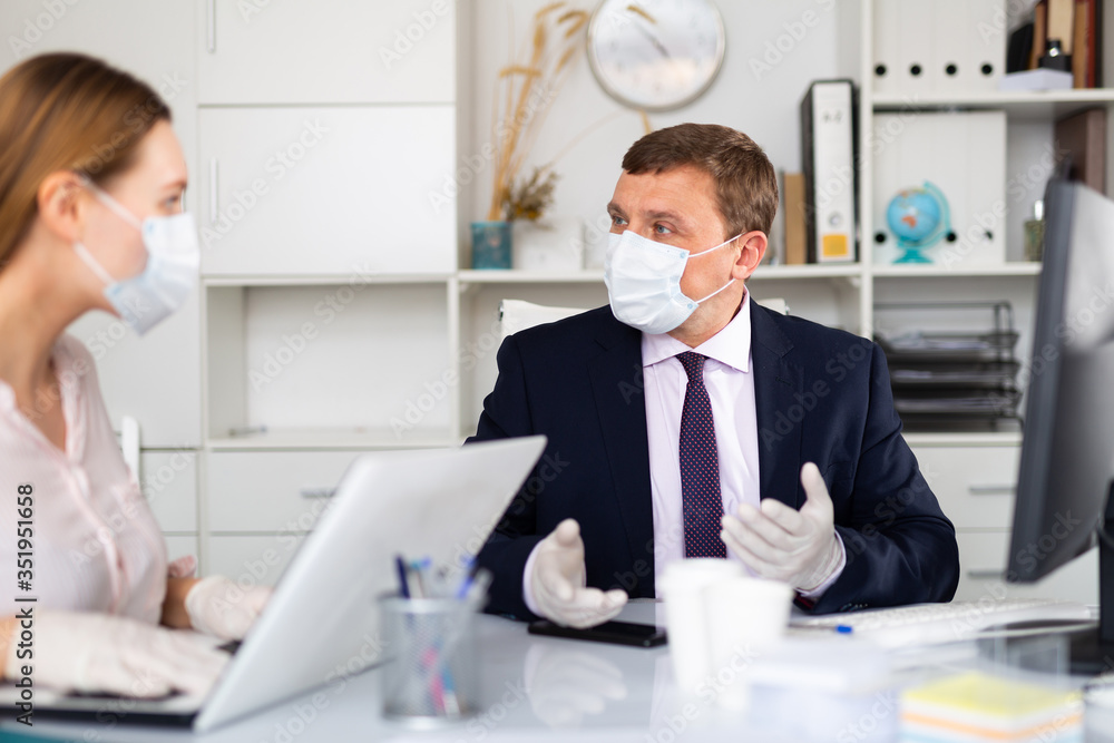 Fototapeta Entrepreneur in medical mask working with female coworker in office