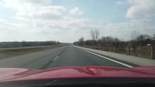 Red Sports Car Driving On Early Spring Day Down Empty Highway